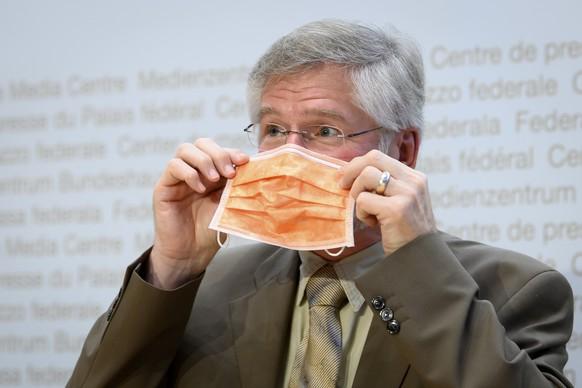 Rudolf Hauri, Praesident der Vereinigung der Kantonsaerztinnen und Kantonsaerzte, setzt einem Schutzmaske auf, nach einer Medienkonferenz des Bundesrates zur aktuellen Lage im Zusammenhang mit dem Coronavirus, am Freitag, 16. Oktober 2020. (KEYSTONE/Anthony Anex)