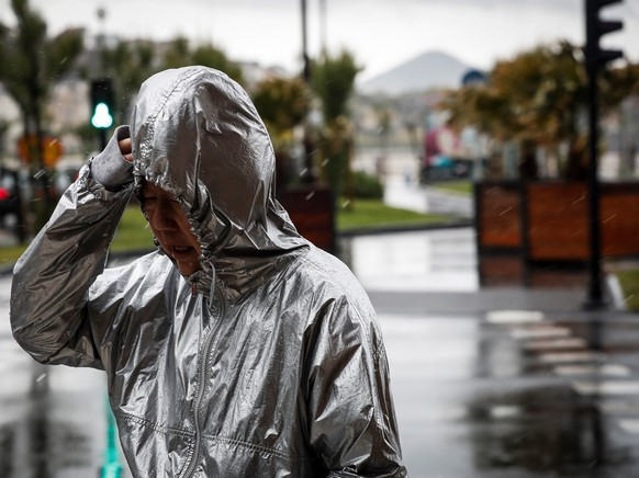 epa07578396 A woman walks across a street during a heavy rainfall in San Sebastian, Basque Country, northern Spain, 17 May 2019. A drop in temperature and rainfalls are expected to hit the region during next weekend.  EPA/Javier Etxezarreta