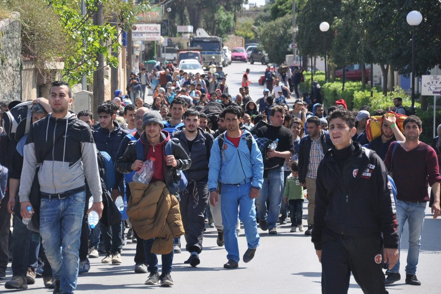epa05239185 Migrants walk in a street of Chios city, on Chios island, Greece, 01 April 2016. A group of more than 500 refugees and migrants, most of them families with children, reportedly broke through a fence and headed out of the Chios hotspot where they were being held.  EPA/ORESTIS PANAGIOTOU