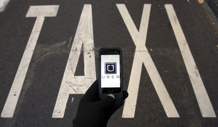 The logo of car-sharing service app Uber on a smartphone over a reserved lane for taxis in a street is seen in this photo illustration taken in Madrid on December 10, 2014. A Madrid judge has ordered U.S.-based online car booking company Uber to cease operations in Spain, the latest ban on the popular service. Taxi drivers around the world consider Uber unfairly bypasses local licensing and safety regulations by using the internet to put drivers in touch with passengers.  REUTERS/Sergio Perez  (SPAIN - Tags: LAW TRANSPORT BUSINESS TELECOMS SCIENCE TECHNOLOGY TPX IMAGES OF THE DAY LOGO)