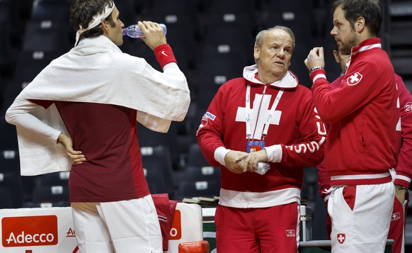 Swiss doctor Roland Biedert, centre, speaks with Swiss Davis Cup Team captain Severin Luethi, right, next to Roger Federer, left, of Switzerland, during a training session of the Swiss Davis Cup Team, prior the Davis Cup Final match between France and Switzerland, in Lille, Switzerland, Thursday, November 20, 2014. The Davis Cup World Group Final France vs Switzerland will take place from 21 to November 23. (KEYSTONE/Salvatore Di Nolfi)
