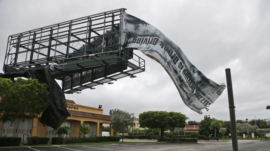 A billboard canvas flaps in the wind after Hurricane Matthew passed off shore, Friday, Oct. 7, 2016, in North Palm Beach, Fla.  Matthew was downgraded to a Category 3 hurricane overnight with the strongest winds of 120 mph just offshore as the storm pushed north, threatening hundreds of miles of coastline in Florida, Georgia and South Carolina.  (AP Photo/Wilfredo Lee)