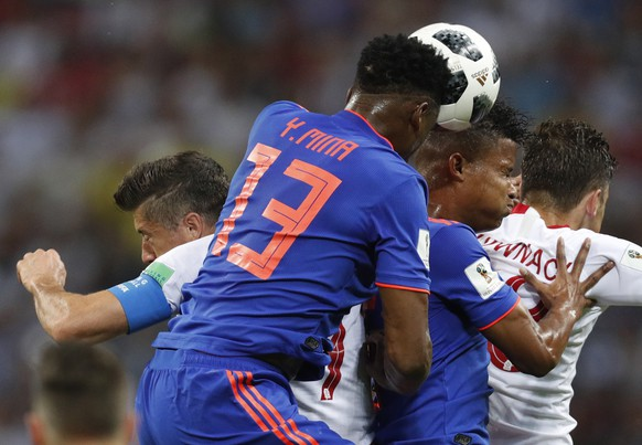 epa06837292 Robert Lewandowski (L) of Poland and Yerry Mina (2-L) of Colombia in action during the FIFA World Cup 2018 group H preliminary round soccer match between Poland and Colombia in Kazan, Russia, 24 June 2018.  (RESTRICTIONS APPLY: Editorial Use Only, not used in association with any commercial entity - Images must not be used in any form of alert service or push service of any kind including via mobile alert services, downloads to mobile devices or MMS messaging - Images must appear as still images and must not emulate match action video footage - No alteration is made to, and no text or image is superimposed over, any published image which: (a) intentionally obscures or removes a sponsor identification image; or (b) adds or overlays the commercial identification of any third party which is not officially associated with the FIFA World Cup)  EPA/ROBERT GHEMENT   EDITORIAL USE ONLY