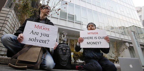 Kolin Burges (R), a self-styled cryptocurrency trader and former software engineer who came from London, and fellow protester Aaron hold placards as they demonstrate against Mt. Gox, in front of the building where the digital marketplace operator is housed in Tokyo February 25, 2014. The website of Mt. Gox appears to be taken down, shortly after six major Bitcoin exchanges released a joint statement distancing themselves from the troubled Tokyo-based bitcoin exchange. Tokyo-based Mt. Gox was a founding member and one of the three elected industry representatives on the board of the Bitcoin Foundation.  REUTERS/Toru Hanai (JAPAN - Tags: BUSINESS CIVIL UNREST SCIENCE TECHNOLOGY)
