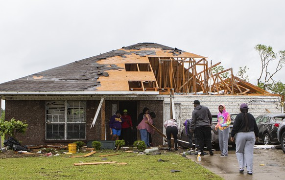 Neighbors and family help to clean a damaged home in Monroe, La. after a tornado ripped through the town just before noon on Sunday, April 12, 2020. (Nicolas Galindo/The News-Star via AP)