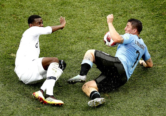 epa06868684 Cristian Rodriguez of Uruguay (R) and Paul Pogba of France in action during the FIFA World Cup 2018 quarter final soccer match between Uruguay and France in Nizhny Novgorod, Russia, 06 July 2018.