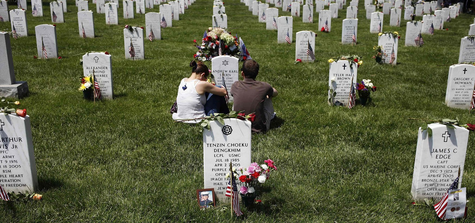 People visit graves in Section 60, where many casualties of the U.S. wars in Iraq and Afghanistan are buried, on Memorial Day at Arlington National Cemetery in Arlington, Virginia May 26, 2014. President Obama marked Memorial Day and the 150th anniversary of the cemetery Monday by laying a wreath to honor the soldiers buried there since the Civil War.  REUTERS/Jonathan Ernst  (UNITED STATES - Tags: POLITICS MILITARY ANNIVERSARY)