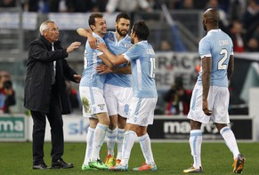 Lazio defender Stefan Radu, of Romania, second from left, celebrates with teammates, from right, Michael Ciani, of France, Alvaro Gonzalez, of Uruguay, and Lazio midfielder Antonio Candreva, and coach Edy Reja, left, after scoring the winning goal during a Serie A soccer match between Lazio and Sassuolo, at Rome's Olympic stadium, Sunday, Feb. 23, 2014. Lazio won 3-2. (AP Photo/Riccardo De Luca)