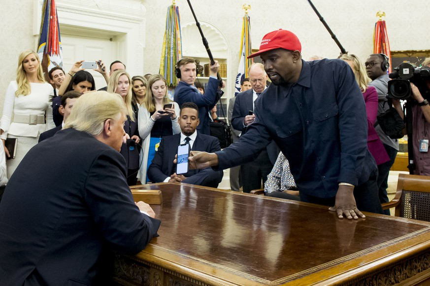 epa07086414 US entertainer Kanye West (R) shows a cell phone depicting the image of an aircraft to US President Donald J. Trump (L) during their meeting in the Oval Office of the White House in Washington, DC, USA, 11 October 2018. Kanye West, who is a Trump supporter, met with the President to discuss prison reform and other issues.  EPA/MICHAEL REYNOLDS