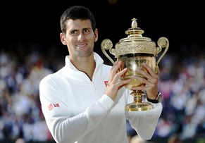 Novak Djokovic of Serbia holds the winners trophy after defeating Roger Federer of Switzerland  in their men's singles final tennis match at the Wimbledon Tennis Championships, in London July 6, 2014.   Djokovic said that he dedicated his win to his former coach who died last year.           REUTERS/Stefan Wermuth (BRITAIN  - Tags: SPORT TENNIS)