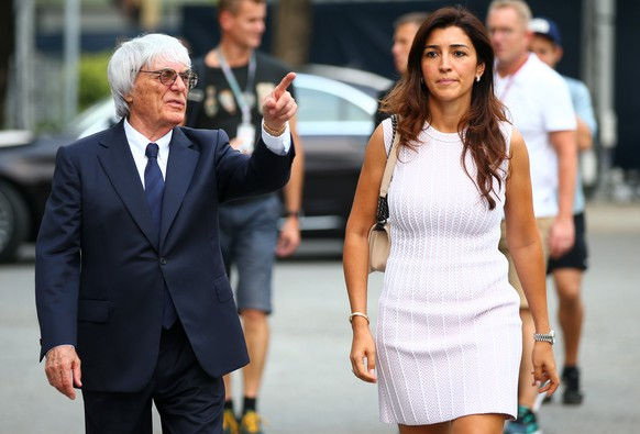 SINGAPORE - SEPTEMBER 18:  F1 supremo Bernie Ecclestone walks through the paddock with his wife Fabiana Flosi during previews ahead of the Singapore Formula One Grand Prix at Marina Bay Street Circuit on September 18, 2014 in Singapore, Singapore.  (Photo by Mark Thompson/Getty Images)