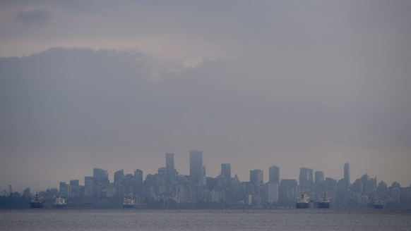 Ships are seen anchored in English Bay with the city of Vancouver, British Columbia, in the background Tuesday, Oct. 30, 2018. (Jonathan Hayward/The Canadian Press via AP)