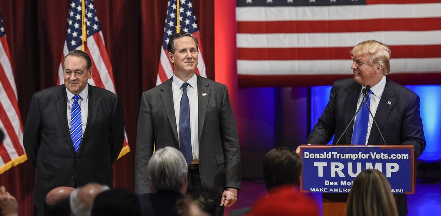 epa05132365 Businessman and Republican presidential candidate Donald Trump (R) stands with Former Arkansas Governor and Republican presidential candidate Mike Huckabee (L) and Former Pennsylvania Senator and Republican presidential candidate Rick Santorum (C) after inviting them on stage at a special event to benefit veterans organizations at Drake University instead of participating in a Fox News debate in Des Moines, Iowa, USA, 28 January 2016. Trump pulled out of the debate over a dispute of who the moderators would be.  EPA/LARRY W. SMITH