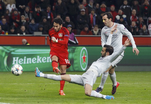 Bayer Leverkusen's Hakan Calhanoglu scores a goal past Atletico Madrid's Diego Godin (front) during their Champions League round of 16, first leg soccer match in Leverkusen February 25, 2015.           REUTERS/Ina Fassbender (GERMANY  - Tags: SPORT SOCCER TPX IMAGES OF THE DAY)