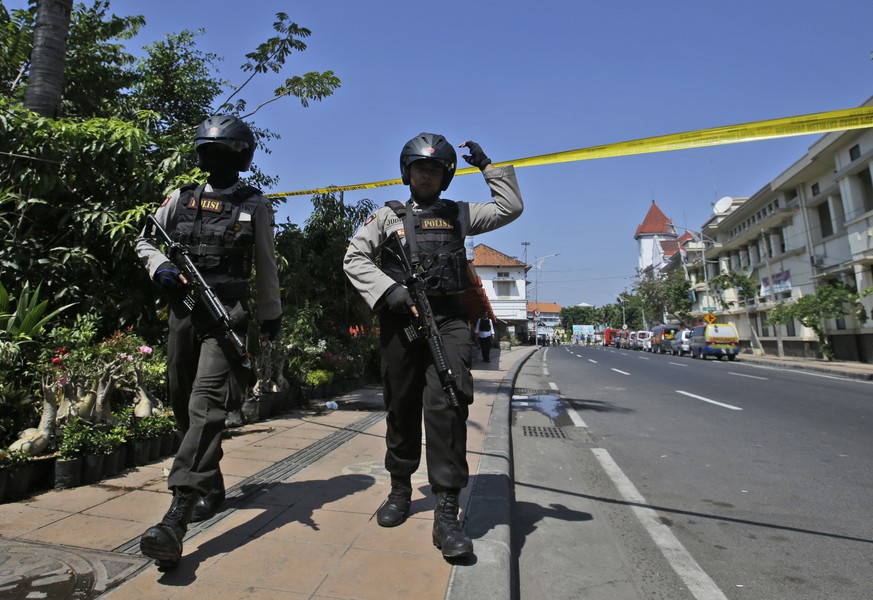 Officers patrol near the local police headquarters following an attack in Surabaya, East Java, Indonesia, Monday, May 14, 2018. The police headquarters in Indonesia's second largest city was attacked Monday by suspected militants who detonated explosives from a motorcycle, a day after suicide bombings at three churches in the city by members of one family killed a number of people. (AP Photo/Achmad Ibrahim)