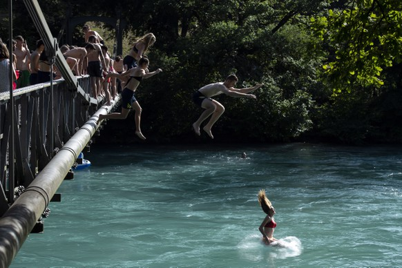 epaselect epa07676475 People jump from a bridge in the Aare River during the sunny and warm weather, in Bern, Switzerland, 27, June 2019. The forecasts predict hot weather in Switzerland with the maximum temperature at 38 degrees Celsius.  EPA/ANTHONY ANEX