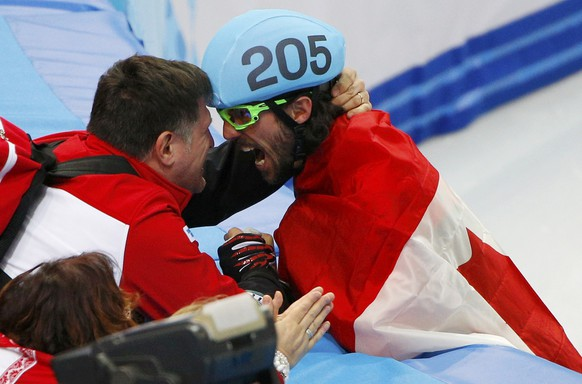 Charles Hamelin (R) of Canada celebrates his victory in the men's 1,500 metres short track speed skating finals event at the Iceberg Skating Palace during the 2014 Sochi Winter Olympics February 10, 2014.           REUTERS/Brian Snyder (RUSSIA  - Tags: SPORT SPEED SKATING OLYMPICS)