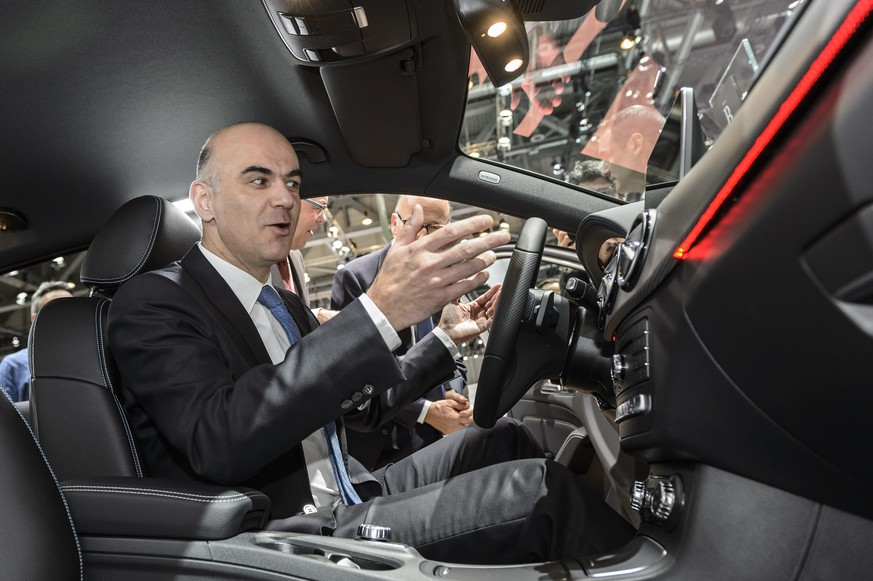 Swiss federal Councillor Alain Berset, left, sits in a Mercedes car shown by Marcel Guerry, CEO of Mercedes-Benz Switzerland, right, during the opening of the 86th Geneva International Motor Show in Geneva, Switzerland, Thursday, March 03, 2016. The Motor Show will open its gates to the public from 3rd to 13th March presenting more than 200 exhibitors and more than 120 world and European premieres. (KEYSTONE/Martial Trezzini)
