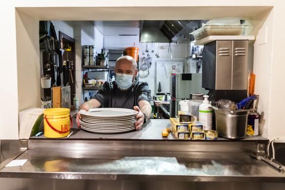 Un cuisinier range la cuisine dans le Restaurant de la Cigogne avant la fermeture lors de la crise du Coronavirus (Covid-19) le dimanche 1 novembre 2020 a Delemont. Face a la deuxieme vague de la pandemie du (Covid-19), le gouvernement jurassien a declare l'etat de necessite. Des lundi, les bars, et les restaurants, sont fermes. (KEYSTONE/Jean-Christophe Bott)