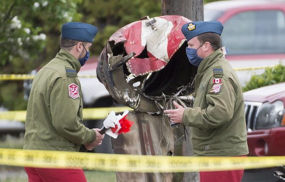 Canadian Forces Snowbird captains Erik Temple, right, and Joel Wilson check out the crash scene of a Canadian Forces Snowbird plane in Kamloops, Canada, Sunday, May 17, 2020. A Canadian aerobatic jet crashed into the British Columbia neighborhood Sunday during a flyover intended to boost morale during the pandemic, killing one crew member, seriously injuring another and setting a house on fire. (Jonathan Hayward/The Canadian Press via AP)