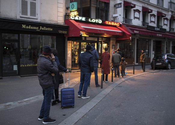 People with a protective masks line up using social distancing to queue at a supermarket in Paris, Monday, March 16, 2020. France's government announced Saturday closing restaurants, bars and other establishments to limit the spread of the new coronavirus. For most people, the new coronavirus causes only mild or moderate symptoms, such as fever and cough. For some, especially older adults and people with existing health problems, it can cause more severe illness, including pneumonia. (AP Photo/Rafael Yaghobzadeh) France Virus Outbreak