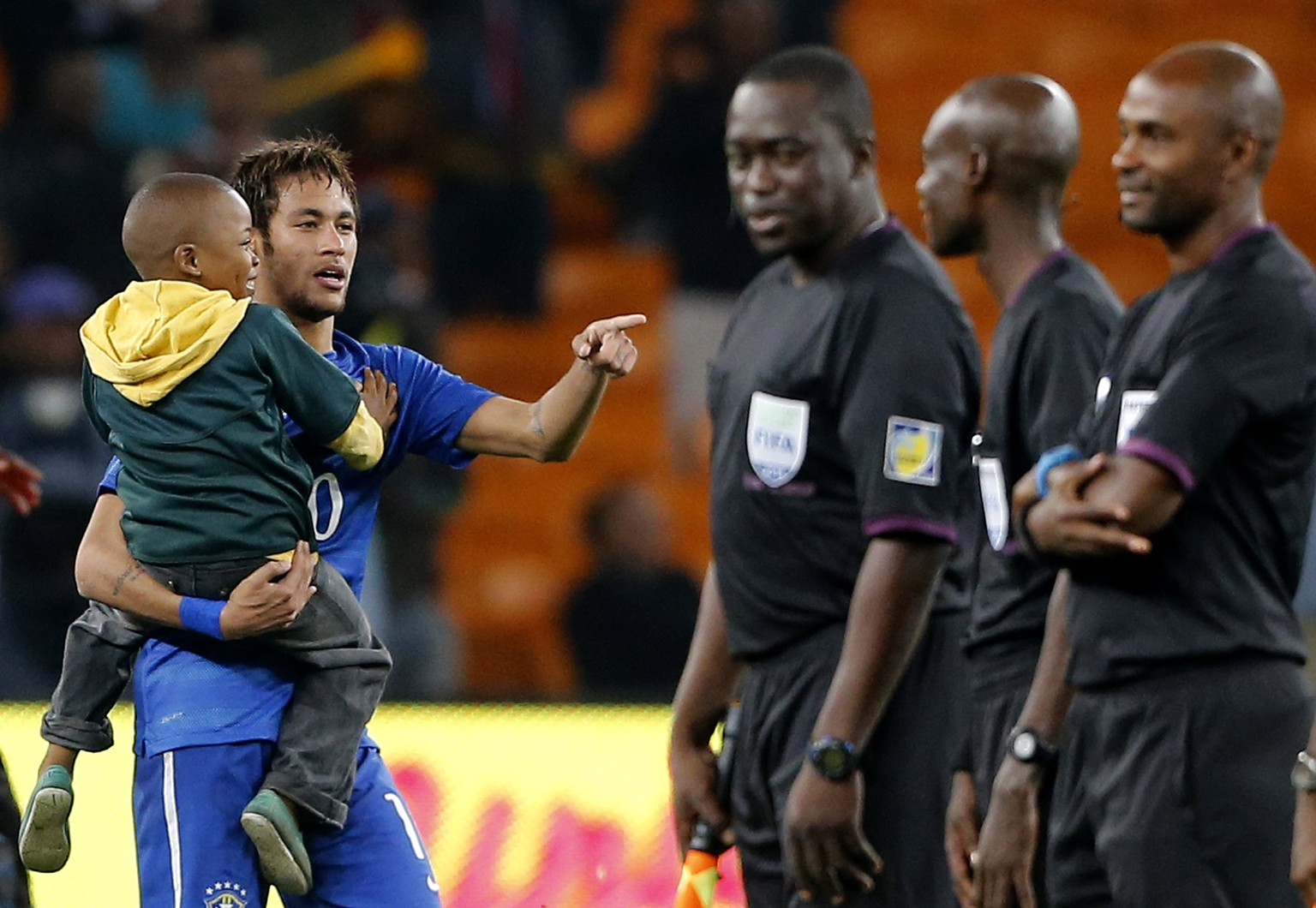 Brazil's Neymar carries a young soccer fan at the end of their international friendly soccer match against South Africa at the First National Bank (FNB) Stadium, also known as Soccer City, Johannesburg March 5 2014. REUTERS/Siphiwe Sibeko (SOUTH AFRICA - Tags: SPORT SOCCER)