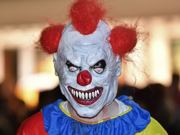 A man wears a Halloween horror clown costume at the zombie walk in Essen, Germany, Tuesday, Oct. 31, 2017. Hundreds of young people celebrate Halloween at Germany's biggest horror walk through the city center of Essen. (AP Photo/Martin Meissner)