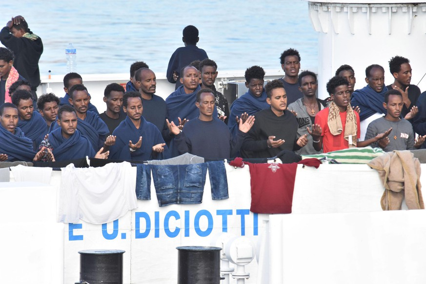 epaselect epa06963777 Migrants pray as they wait to disembark from Italian Coast Guard ship Diciotti in the port of Catania, Italy, 22 August 2018. Italian Interior Minister Matteo Salvini said on 20 August the rescued migrants are only allowed to disembark if the European Union member states agree to take in some of them. The ship entered on 20 August in the port of Catania with the 177 migrants rescued from a barge off Lampedusa island.  EPA/ORIETTA SCARDINO