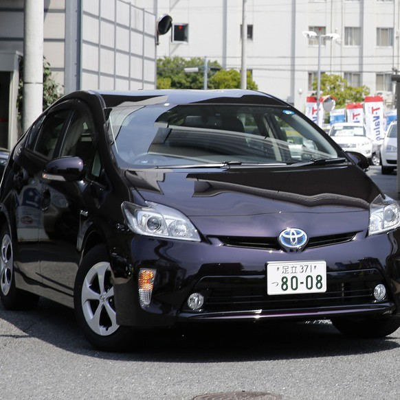 A Toyota Motor Corp Prius hybrid car (L) goes past a Volkswagen Tiguan car at their dealership in Tokyo July 30, 2014. Volkswagen is closing in on Toyota Motor Corp as the global leader in vehicle sales, with a rapid expansion drive in China - the world's biggest auto market - while Toyota curbs growth to focus on shoring up quality. REUTERS/Toru Hanai (JAPAN - Tags: BUSINESS TRANSPORT)