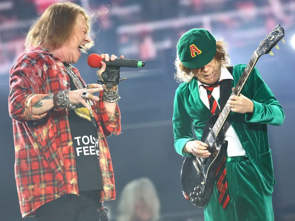 epa05341050 AC/DC lead guitarist Angus Young (R)and singer Axl Rose perform during a concert as part of the tour of the Australian band in Leipzig, Germany, 01 June 2016.  EPA/JAN WOITAS