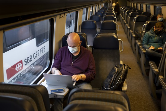 epa09091964 Passenger wearing protective mask works on a laptop as he rides a Swiss Federal Railways SBB CFF FFS train during the coronavirus disease (COVID-19) outbreak, in Neuchatel, Switzerland, 23 March 2021. Switzerland as many countries in Europe impose coronavirus restrictions to fight against the spread of coronavirus COVID-19.  EPA/LAURENT GILLIERON
