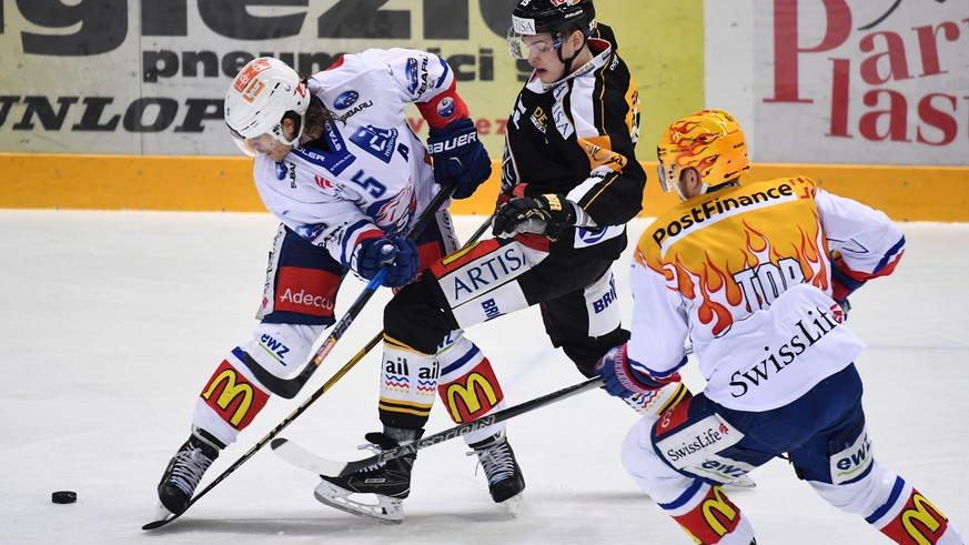 Zurich's player Severin Blindenbacher, left, fights for the puck with Lugano's player Gregory Hofmann, center, during the second leg of the Playoffs quarterfinals game of National League A (NLA) Swiss Championship between Switzerland's HC Lugano and ZSC Lions, on Tuesday, March 7, 2017, in the Resega Stadium in Lugano. (KEYSTONE/Ti-Press/Gabriele Putzu)