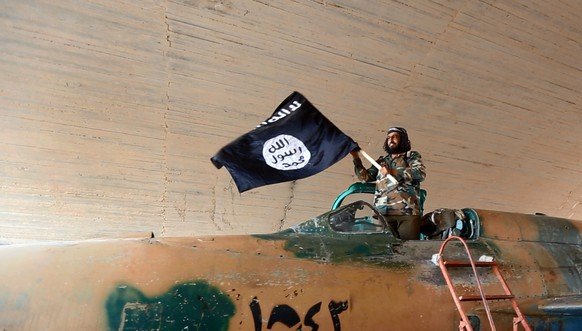 FILE - This undated file image posted on Wednesday, Aug. 27, 2014 by the Raqqa Media Center of the Islamic State group, a Syrian opposition group, which has been verified and is consistent with other AP reporting, shows a fighter of the Islamic State group waving their flag from inside a captured government fighter jet following the battle for the Tabqa air base, in Raqqa, Syria on Sunday. The Islamic State group is a far superior threat today than al-Qaida was in 2001. It is richer, operates a modern, effective media arm and holds much more territory than al-Qaida ever did. And while al-Qaida operated on the basis of a loose network of various cells in different countries _ a decentralization that worked in its favor in the beginning _ the group eventually could no longer centralize its command in a coherent way. (AP Photo/ Raqqa Media Center of the Islamic State group, File)