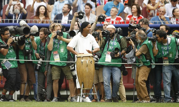 Former Brazilian soccer player Ronaldinho, centre, surrounded by photographers plays on the drums as he takes part in the closing ceremony before the start of the the final match between France and Croatia at the 2018 soccer World Cup in the Luzhniki Stadium in Moscow, Russia, Sunday, July 15, 2018. (AP Photo/Francisco Seco)
