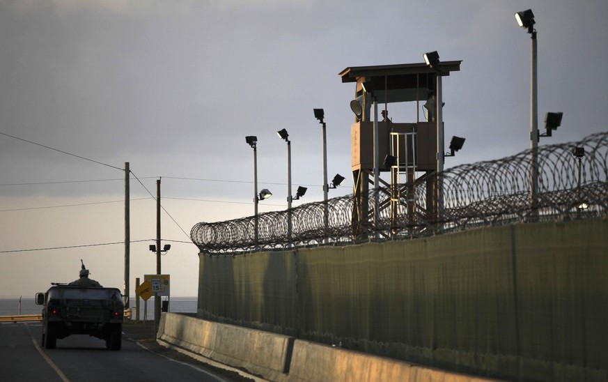 FILE – In this March 30, 2010, file photo, reviewed by the U.S. military, a U.S. trooper stands in the turret of a vehicle with a machine gun, left, as a guard looks out from a tower at the detention facility of Guantanamo Bay U.S. Naval Base in Cuba. President Barack Obama's quest to close the prison at Guantanamo Bay, perhaps by moving some detainees to the United States, has sparked an unusual alliance between his congressional critics and liberal-leaning advocacy groups that say changing the detention facility's ZIP code won't solve the problem.  (AP Photo/Brennan Linsley, File)