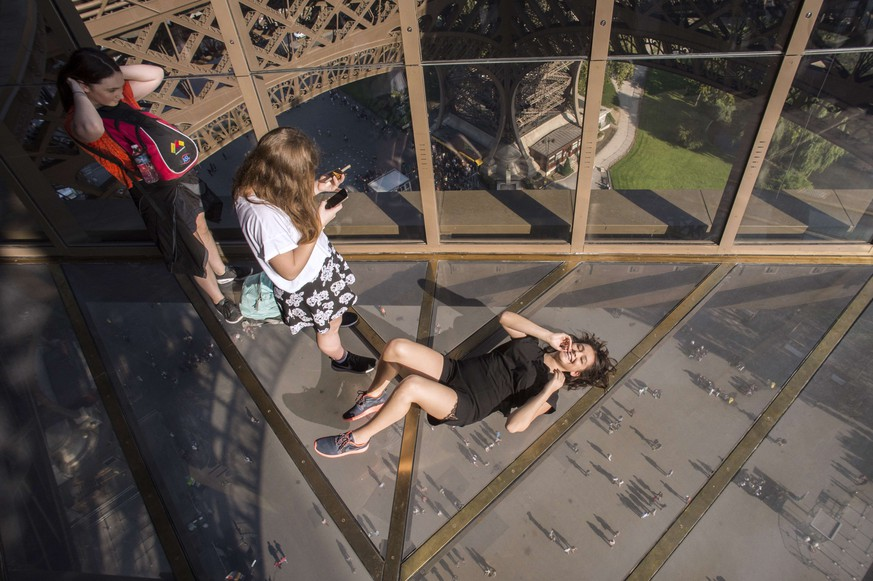 Visitors take photos as they lie down on the new glass floor at the Eiffel Tower in Paris on October 3, 2014. The Eiffel Tower is inaugurating a new glass floor on October 6 that is turning the heads of the millions of tourists who flock to Paris's best-known landmark every year. AFP PHOTO LIONEL BONAVENTURE