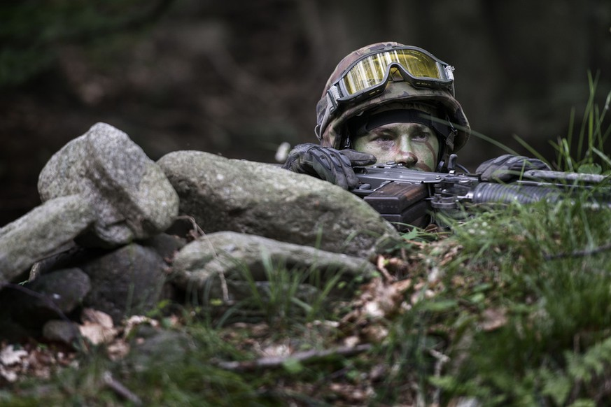 A grenadier recruit peers over the edge of the trench, pictured during an urban warfare exercize of the grenadier recruit school of the Swiss Armed Forces in Isone, canton of Ticino, Switzerland, on July 2, 2013. (KEYSTONE/Christian Beutler)  Ein Grenadier-Rekrut blickt ueber den Rand einer Senkung, aufgenommen bei einer Haeuserkampf-Uebung der Grenadier-Rekrutenschule der Schweizer Armee in Isone, Kt. Tessin, am 2. Juli 2013. (KEYSTONE/Christian Beutler)