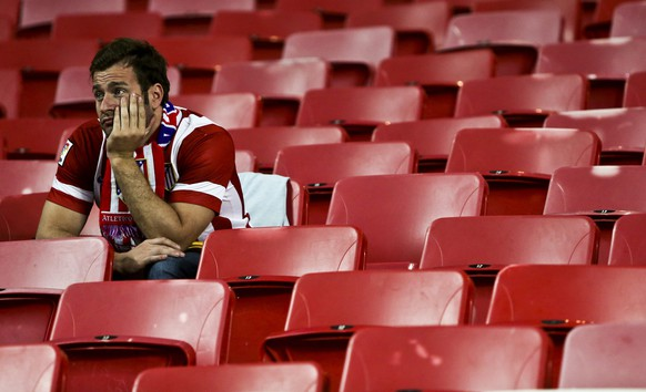 epa04223514 An Atletico Madrid supporter looks dejected after the UEFA Champions League final between Real Madrid and Atletico Madrid at Luz stadium in Lisbon, Portugal, 24 May 2014. Real Madrid become European champions for the 10th time by beating city rivals Atletico Madrid 4-1 after extra time.  EPA/MARIO CRUZ