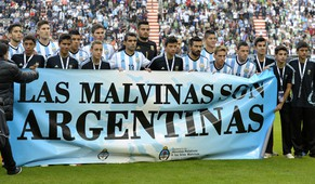 "Argentina's footballers pose for photographers holding a banner reading ""The Malvinas / Falkland Islands are Argentine"" before a friendly football match against Slovenia at La Plata stadium in La Plata, Buenos Aires, Argentina on June 7, 2014 in preparation of the 2014 FIFA World Cup Brazil to be held between June 12 and July 13.  AFP PHOTO / Alejandro PAGNI"