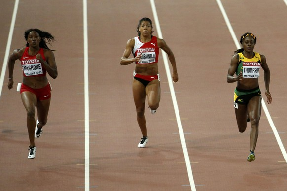Elaine Thompson of Jamaica (R) runs to win ahead of Candyce McGrone of the U.S. (L) and Mujinga Kambundji of Switzerland (C) in their women's 200 metres semi-final during the 15th IAAF World Championships at the National Stadium in Beijing, China, August 27, 2015.     REUTERS/Fabrizio Bensch
