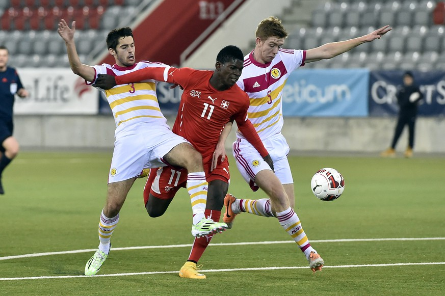 Switzerland's Breel Embolo, center, fights for the ball against Scotland's Stephen Hendrie, left, and Stuart Findlay during the under 21 international friendly soccer match between Switzerland and Scotland at the Stockhorn Arena in Thun, Switzerland, pictured on November 18, 2014. (KEYSTONE/Peter Schneider)