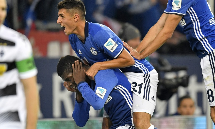 Schalke's Alessandro Schoepf jumps on scorer Breel Embolo, center, to celebrate their side's 2nd goal during the German Bundesliga soccer match between FC Schalke 04 and Borussia Moenchengladbach in Gelsenkirchen, Germany, Sunday, Oct. 2, 2016. (AP Photo/Martin Meissner)