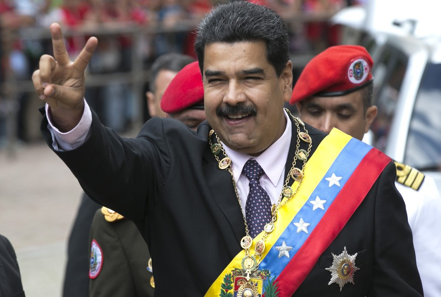 Venezuela's President Nicolas Maduro flashes a victory sign to supporters as he arrives to the Supreme Court to deliver his annual state of the nation report in Caracas, Venezuela, Sunday, Jan. 15, 2017. For more than half a century, Congress had been the body responsible for receiving the president's annual report, as established by the constitution, but the legislature lost that power by decision of the court, which authorized last week for Maduro to present his speech to magistrates. (AP Photo/Ariana Cubillos)