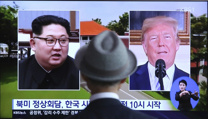 A man watches a TV screen showing file footage of U.S. President Donald Trump, right, and North Korean leader Kim Jong Un during a news program at the Seoul Railway Station in Seoul, South Korea, Monday, June 11, 2018.  Final preparations are underway in Singapore for Tuesday's historic summit between President Trump and North Korean leader Kim, including a plan for the leaders to kick things off by meeting with only their translators present, a U.S. official said.  The signs read: