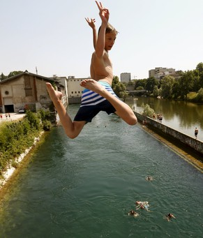 A boy jumps during hot temperatures from a bridge into the Limmat river in Zurich July 3, 2015. On the right is the Sihl river and the headquarters of Swiss retailer Migros.  REUTERS/Arnd Wiegmann