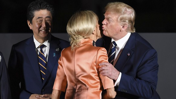epa07679868 US President Donald Trump (R) greets French First Lady Brigitte Macron (C), during the official family picture at a cultural event at the Osaka Geihinkan, during the G20 summit in Osaka, Japan, 28 June 2019. The leaders of the world's largest economies gathered in Osaka for the fourteenth meeting of Group of Twenty (G20).  EPA/LUKAS COCH  AUSTRALIA AND NEW ZEALAND OUT