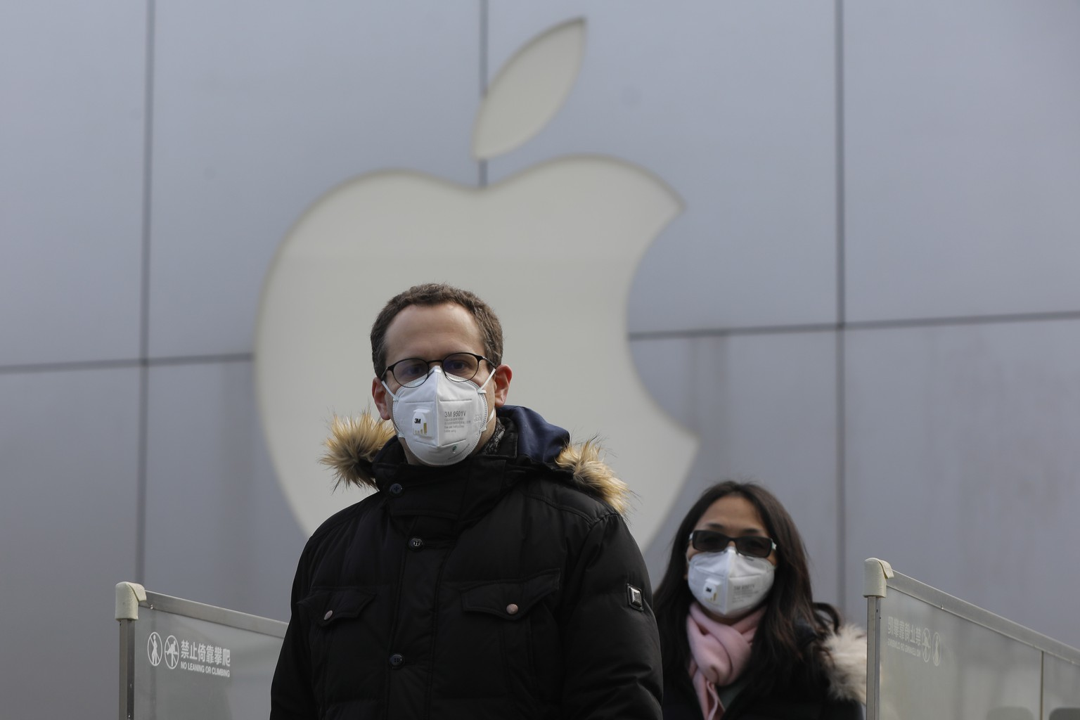 epaselect epa08186957 People wear masks as they walk past a closed Apple store at Sanlitun in Beijing, China, 02 February 2020. Apple announced the closure of its stores, corporate offices and contact centers on mainland China until 09 February, due to the novel coronavirus outbreak in the nation.  EPA/WU HONG