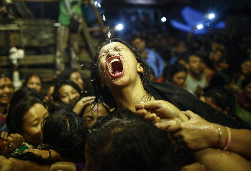 epa05544814 Nepalese women and young girls struggle to drink homemade alcohol poured through a pipe sticking out of the mouth of Swet Bhairab, a god of Power, during the Indra Jatra festival at Basantapur Durbar Square in Kathmandu, Nepal, 17 September 2016. Hundreds of women and young girls gathered to drink alcohol as a blessing from idol of Swet Bhairab which they believes will keep them free from all diseases. The Indra Jatra festival is celebrated to honor Indra, the king of gods and god of rains. The festival also marks the end of the monsoon.  EPA/NARENDRA SHRESTHA