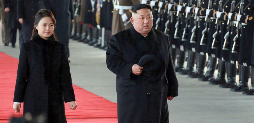 In this Monday, Jan. 7, 2019, photo provided on Tuesday, Jan. 8, 2019 by the North Korean government, North Korean leader Kim Jong Un walks with his wife Ri Sol Ju at Pyongyang Station in Pyongyang, North Korea, before leaving for China. Kim left for China for a four-day trip, the North's state media reported Tuesday, amid speculation that he may attempt to coordinate his positions with Beijing ahead of his likely summit with U.S. President Donald Trump. Independent journalists were not given access to cover the event depicted in this image distributed by the North Korean government. The content of this image is as provided and cannot be independently verified. Korean language watermark on image as provided by source reads:
