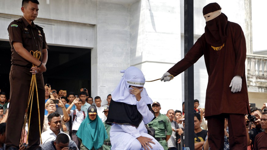 epa06680856 An Acehnese woman covers her face as she is caned in public for violating sharia law in Banda Aceh, Indonesia, 20 April 2018. Aceh's provincial government has decided to end the caning sentence in public to prevent them from being witnessed by children or recorded and spread in social media.  EPA/RAIHAL FAJRI